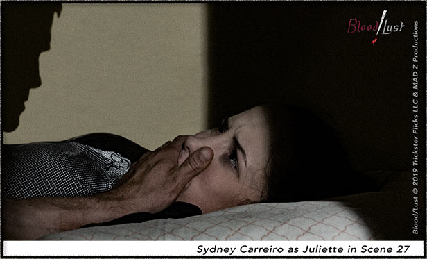 Juliette in bed with a hand on her month.